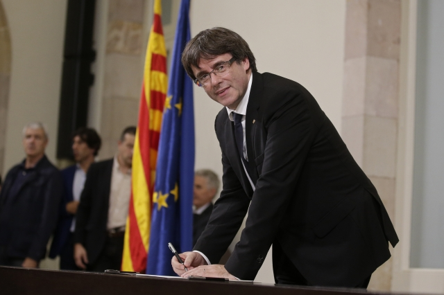 Catalan leader stakes claim to independence, then delays it